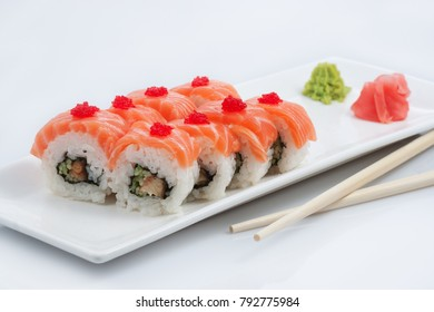 sushi or rolls in assortment on a long plate, wooden sticks, red ginger and wasabi, on white background