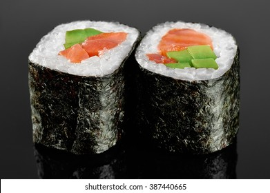 Sushi rolls with avocado, salmon and spicy sauce on black background.