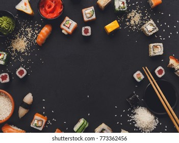 Sushi and rolls background, frame on black, top view, copy space. Colorful japanese restaurant food set
