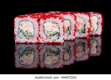 Sushi rolls with crab sticks and cucumber on black background
