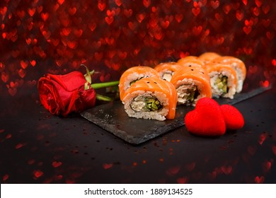 Sushi rolls laid out a black plate on black background. Red rose and red hearts on black table with red bokeh background. Creative greetings. concept of Japanese cuisine for Valentines Day