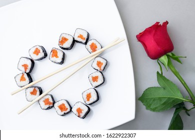 Sushi rolls laid out in the shape of a heart on a white plate. Red rose on a gray background. Creative greetings. The concept of Japanese cuisine for Valentine's Day, greeting card, banner. Copy space