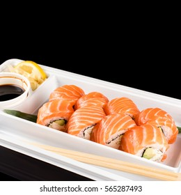 Sushi rolls made of fresh raw salmon, cream cheese and avocado in white plastic container ready to eat on black background with reflections.