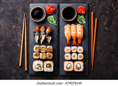 Sushi rolls, maki, nigiri Set served for two on black stone slate on dark background