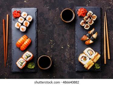 Sushi rolls, maki, nigiri Set served for two on black stone slate on dark background copy space