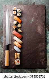 Sushi rolls and nigiri with Japanese knife on stone slate background