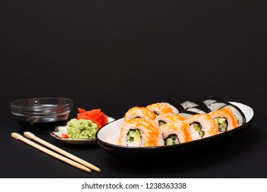 Sushi rolls with nori, rice, pieces of avocado, cucumber, flying fish roe on ceramic plate. Plate with red pickled ginger and wasabi. Bowl with soy sauce and wooden sticks. Black background.