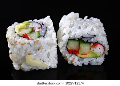 Sushi rolls on the black background, close-up, shallow focus