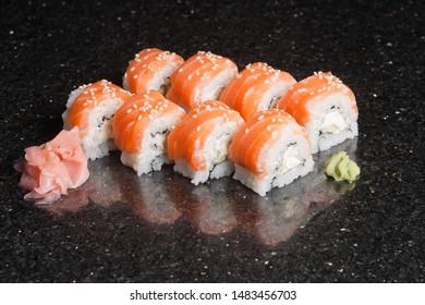 Sushi rolls on black marble background. Fresh Hosomak, Maki, Nigiri, Tempura, Uramaki, Philadelphia pieces with rice, nori and fish. Japanese cusine, Asian food.