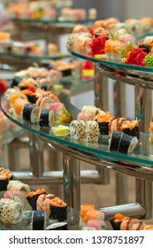 a lot of sushi rolls on the glass buffet. Japan traditional food on table with eastern decor. catering
