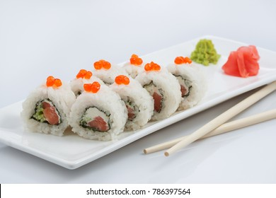 sushi or rolls on a long plate, wooden sticks, red ginger and wasabi, on white background