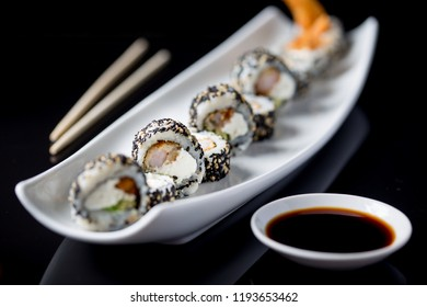 Sushi rolls on white plate. Black background