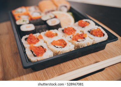 Sushi rolls on a white plate with chopsticks on a white stand, closeup