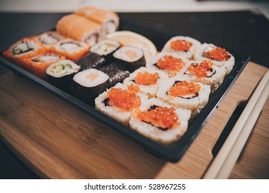 Sushi rolls on a white plate with chopsticks on a white stand, closeup.