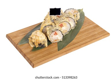 Sushi rolls on wooden Board with leaves of leeks and black sign for logo and name
