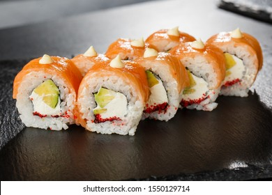 Sushi Rolls with salmon, avocado, flying fish caviar and Cream Cheese inside on black slate isolated. Philadelphia roll sushi with salmon. Sushi menu. Horizontal photo.