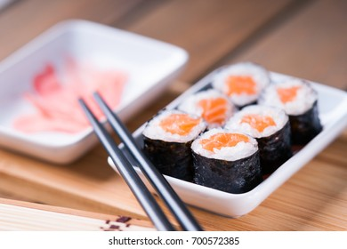 Sushi rolls with salmon, ginger and chopsticks