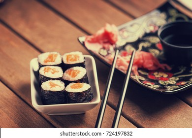 Sushi rolls with salmon, ginger, chopsticks and soy sauce