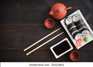 Sushi rolls with salmon and hot tea ceremony on black wooden table