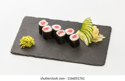sushi rolls with salmon on a black plate isolated on a white background.