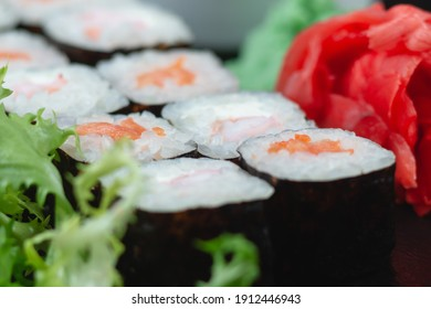 Sushi rolls with salmon, rice, greens and soy sauce