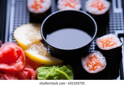 Sushi rolls with salmon, soy sauce, wasabi and ginger