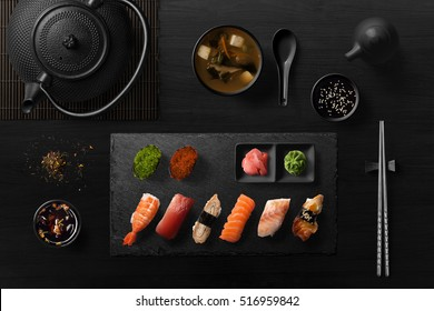 Sushi rolls, sashimi set, miso soup and teapot, on dark wooden table, Japanese food, top view.