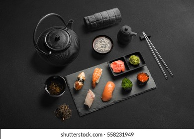 Sushi rolls, sashimi set, miso soup and teapot, on dark wooden table, Japanese food, isometric view.