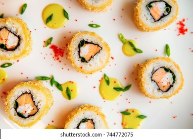 Sushi rolls scattered on white background