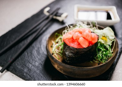 Sushi rolls, seafood delicacy, menu background, Japanese fusion restaurant concept. Japanese food art, expensive meals. Tuna gunkan maki with sauce and chopsticks