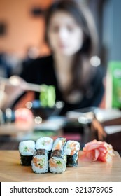 Sushi rolls served on a wooden plate in a restaurant with blurred woman on background, vertical composition. Very shallow DOF, focus is on the first row of rolls.