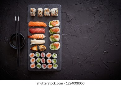 Sushi rolls set with salmon and tuna fish served on black stone board. Top view of traditional japanese cuisine. Asian food on black stone slate with chopsticks.