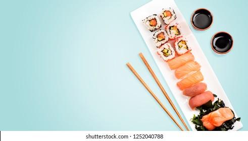 Sushi-Rollen mit Lachs und Thunfisch auf hellblauem Hintergrund von oben. Der Blick auf die traditionelle japanische Küche. Das asiatische Restaurant serviert moderne Speisen.