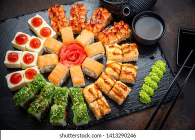Sushi rolls set served on black stone slate on dark background. Japanese menu. Horizontal top view from above