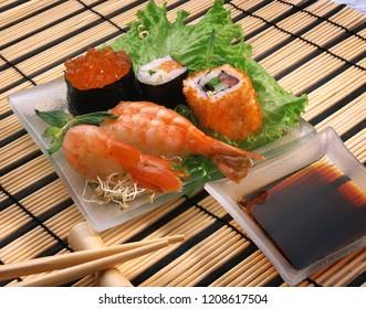 Sushi, rolls, shrimps, red caviar, soy sauce, Japanese chopsticks on Japanese bamboo napkin
