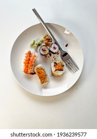 Sushi rolls  and soy sauce with fork on plate on white background top view