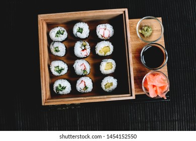 Sushi rolls with vegetable filling over dark bamboo background