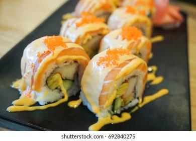 Sushi salmon roll with topped spicy sauce on black dish - japanese food