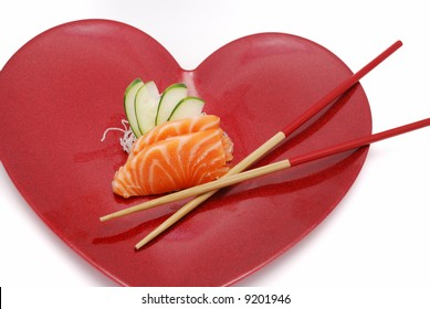 Sushi sashimi salmon on heart plate with chopsticks