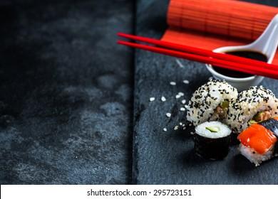Sushi selection on black slate, food border background