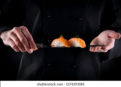 Sushi served on japanese knife in chef hands on dark background. Decorated salmon sashimi nigiri. Traditional japanese food. Copy space for text