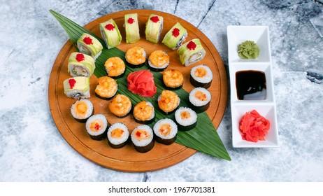 Sushi set. Avocado sushi rolls, shrimps maki sushi rolls, maki sushi on wooden tray with leaf and gari isolated on marble. Wasabi, soy sauce and gari in plate isolated on marble.