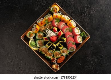 Sushi set with different types of rolls and sashimi made from eel, salmon, tuna, shrimp, red caviar and tobiko flying fish roe. Pan-Asian and Asian food and dishes on a black concrete kitchen table.