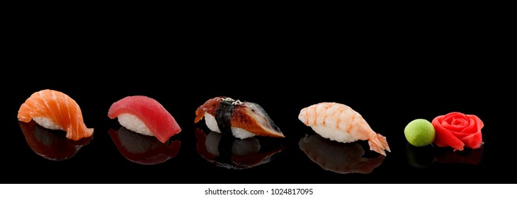 Sushi set with ginger and wasabi over dark background.