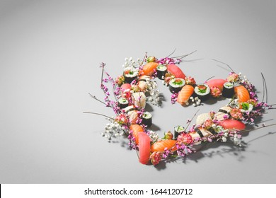 Sushi set. Heart made of sushi and flowers. Love sushi. Valentines Day (14 February), Woman's day (8 March) or spring concept. Creative romantic. Japanese sushi set on gray background. Copy space