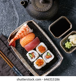 Sushi Set nigiri and sushi rolls in dark ceramic plate with soy sauce, iron teapot and chopsticks over black stone texture background. Top view with space. Japan menu. Square image