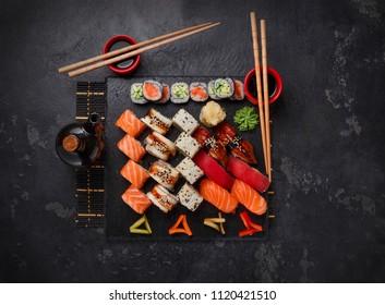 Sushi Set nigiri and sushi rolls on black stone slate plate board. Top view.