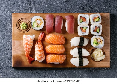 Sushi Set nigiri and sushi rolls on wooden serving board over black stone texture background. Top view with space. Japan menu