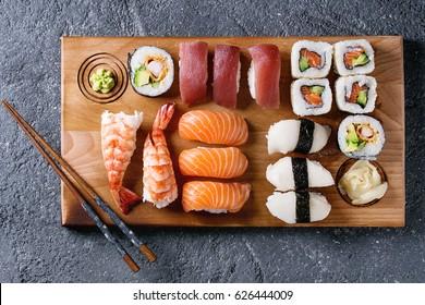 Sachets de sushi Ensemble de nigiri et de rouleaux de sushi sur fond de service en bois avec baguettes sur fond texture en pierre noire. Vue de dessus avec place. Menu Japon