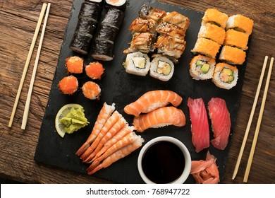 Sushi Set nigiri, sushi rolls and sashimi served on stone slate.